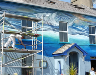 Barry Sweeney painting murals on Eithnas by the Sea restaurant